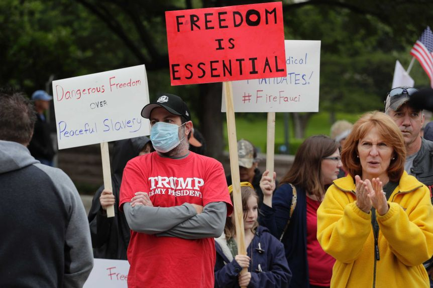 People protest in Austin, Texas carrying placards for the reopening of the country.