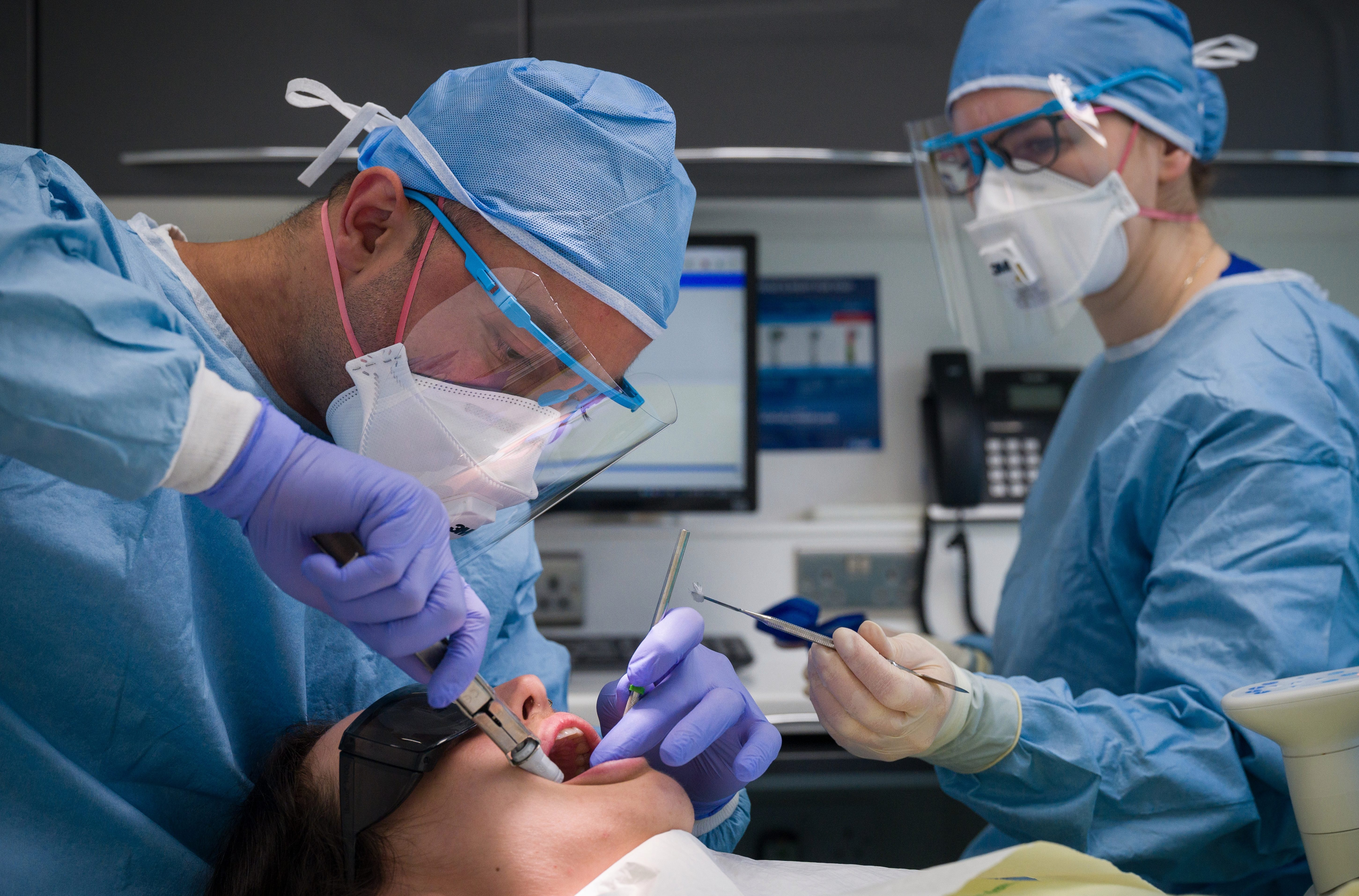 Dentists carry out a procedure on a patient in one of the six surgery rooms at East Village dental practice in London today