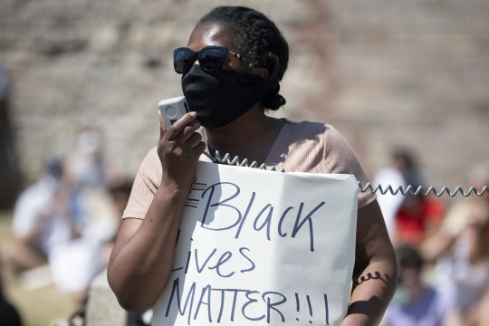 CARDIFF, WALES - MAY 31: A woman speaks into a megaphone while holding a sign which says 'black lives matter' during a protest outside Cardiff Castle in response to the death of George Floyd on May 31, 2020, in Cardiff, Wales. African-American George Floyd, 46, died in police custody after being arrested outside a shop in Minneapolis, Minnesota. Footage of the arrest shows a white police officer, Derek Chauvin, kneeling on George Floyds neck while he was pinned to the floor. The death has lead to protests across the US. (Photo by Matthew Horwood/Getty Images).