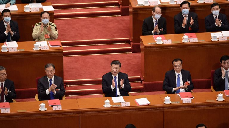 China's President Xi Jinping (C) applauds after the National People's Congress approves a proposal to draft a Hong Kong security law