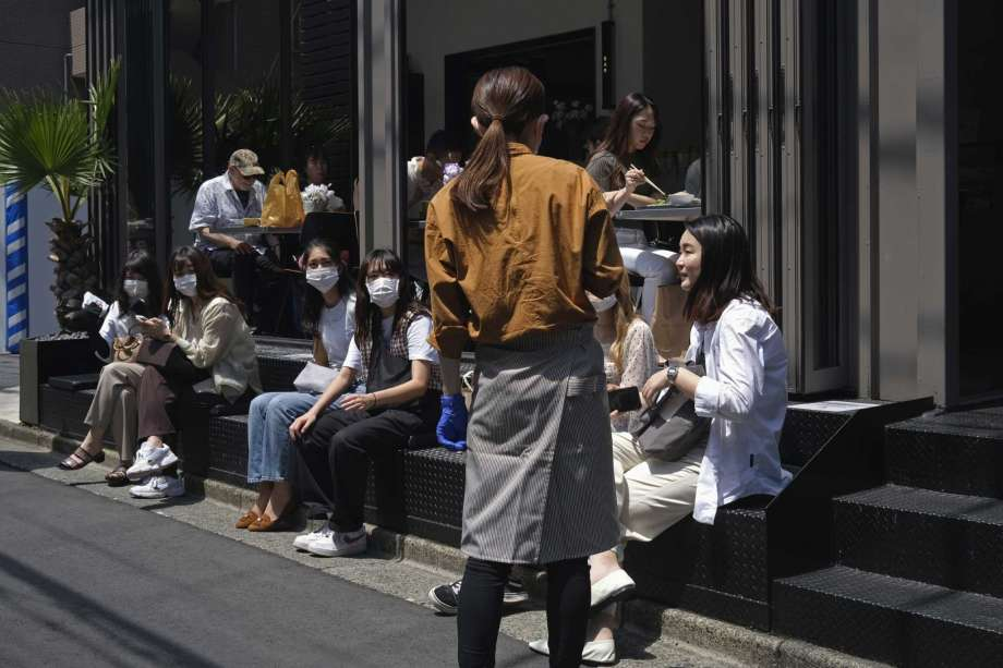 A server with a protective face mask and gloves takes orders as customers waits outside a restaurant to be seated, Sunday, June 7, 2020, in Tokyo. As Japanese return to schools, shops and offices reconfigured to help prevent new coronavirus infections with ample use of plastic screens, masks and reminders to keep their distance, access to faster testing is crucial, officials say. Photo: Kiichiro Sato, AP / Copyright 2020 The Associated Press. All rights reserved