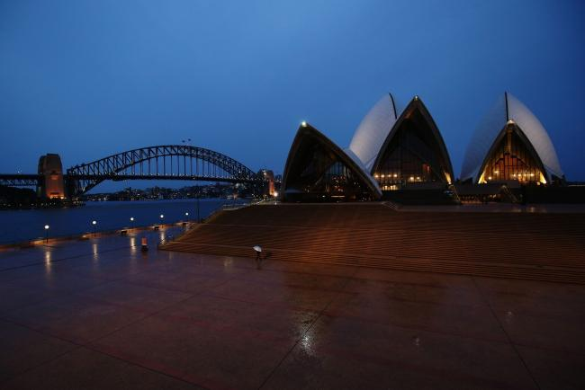 © Bloomberg. A pedestrian holding an umbrella walks along the Sydney Opera House forecourt during a partial lockdown imposed due to the coronavirus, at night in Sydney, Australia, on Friday, April 3, 2020. Australia's Prime Minister Scott Morrison said the government is close to announcing an agreement that will see rent relief for businesses hit by the coronavirus outbreak. The government wants a new industry code of practice for commercial tenancies, so any decline in revenue for a small- or medium-sized enterprise is reflected in a proportionate drop in rent they have to pay. Photographer: Brendon Thorne/Bloomberg