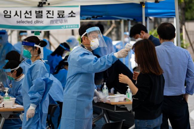 © Bloomberg. A medical worker in protective gear checks a temperature of a woman at a temporary coronavirus testing station in Seoul, South Korea, on Friday, May 29, 2020. In the wake of the new cluster, the South Korean government said it was temporarily closing public museums, parks and galleries in the Seoul metropolitan area and may consider stronger social distancing measures if the situation worsens.