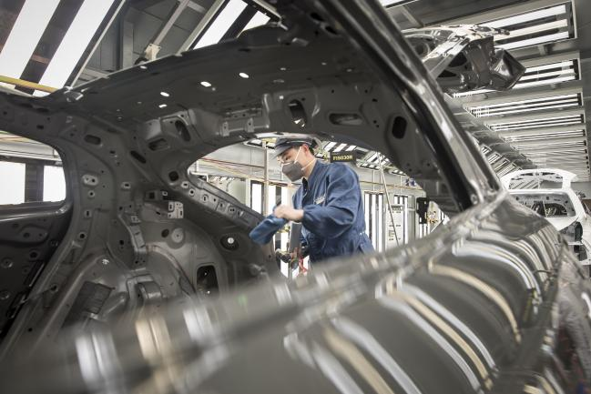 © Bloomberg. An employee wearing a protective mask works on a Lynk & Co. 05 crossover sport utility vehicle (SUV) in the paint shop at the Geely Automobile Holdings Ltd. plant in Ningbo, Zhejiang Province, China, on Tuesday, April 28, 2020. China's manufacturing purchasing managers' index (PMI) jumped to 52 in March, from an historic low of 35.7 in February as activity rebounded from disruptions caused by the coronavirus and containment measures. Photographer: Qilai Shen/Bloomberg