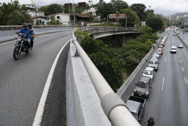 © Bloomberg. A line of cars waits to refuel at a Petroleos de Venezuela gas station in Caracas on June 1.