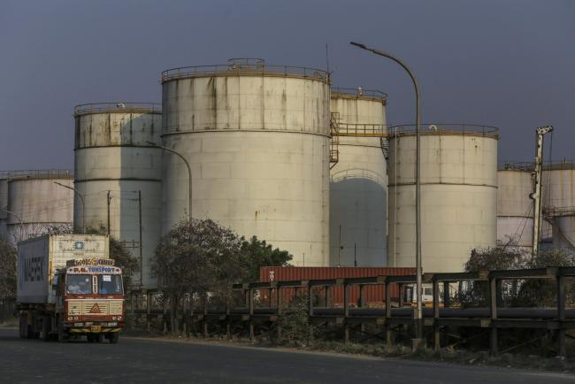 © Bloomberg. A container truck travels past oil storage tanks at Jawaharlal Nehru Port, operated by Jawaharlal Nehru Port Trust (JNPT), in Navi Mumbai, Maharashtra, India, on Monday, March 30, 2020. As billions of people stay home in the the world's major economic centers, consumption of everything from transport fuel to petrochemical feedstocks is in freefall. Refiners that have already been filling up their storage tanks with unsold products now have little choice but to partially shut down their plants. Photographer: Dhiraj Singh/Bloomberg