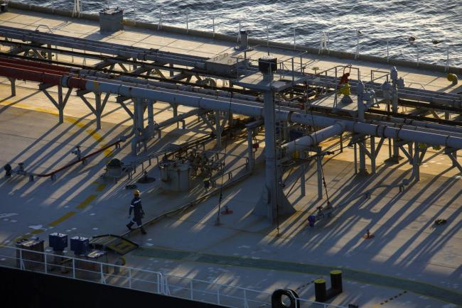 © Bloomberg. A crew member walks on the deck of an oil tanker anchored in the Pacific Ocean in this aerial photograph taken above Long Beach, California, U.S., on Friday, May 1, 2020. The volume of oil on vessels located just offshore the state peaked at 26 million barrels over the weekend, about a quarter of the world's daily consumption, before dropping to 22 million barrels on Monday, according to Paris-based Kpler SAS, which tracks tanker traffic. Photographer: Patrick T. Fallon/Bloomberg