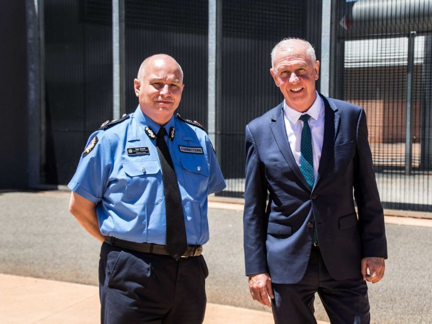 Two men in high-ranking roles standing outside prison walls.