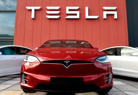 Red Tesla car with two white Teslas behind