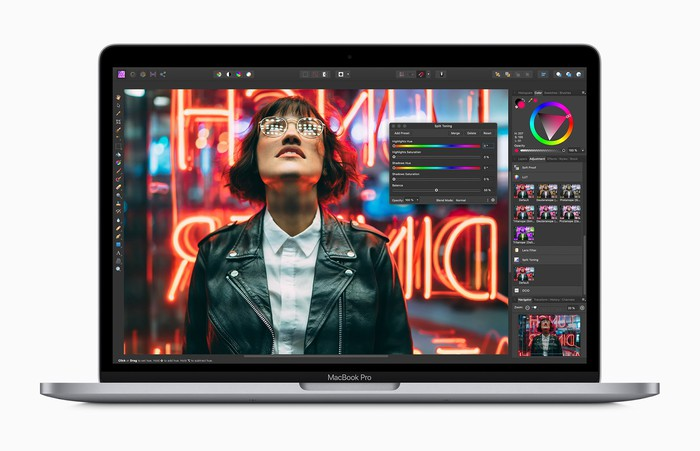A woman at night wearing a leather jacket and glasses looking upward, shown on an Apple Macbook Pro.