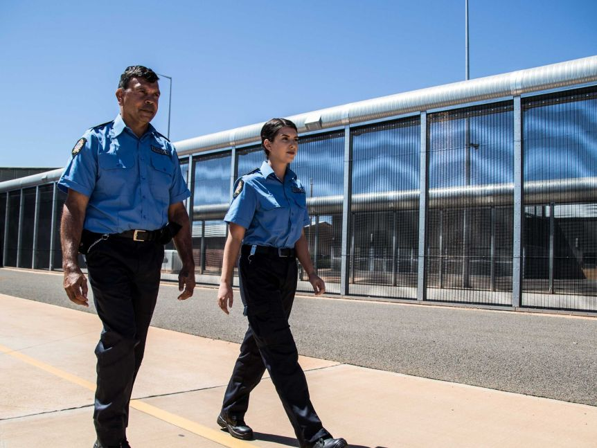Two prison guards in uniform walking along the fence line at a jail.