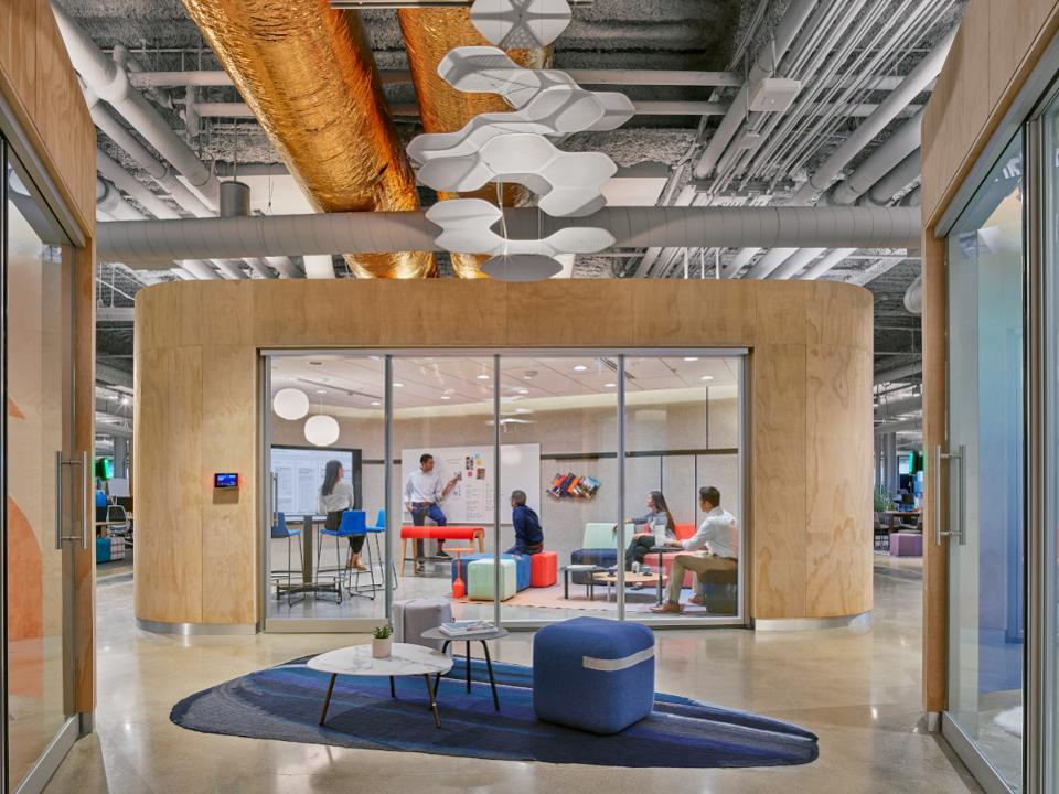 Colorful, technology-inspired conference room in modern setting with people interacting.