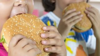 Two children eat burgers