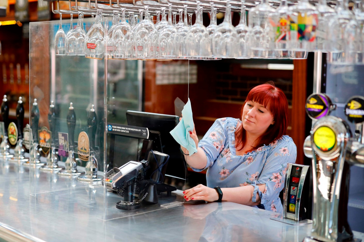 A member of staff at a Wetherspoons pub in north London cleans a perspex barrier put in place for pubs to reopen