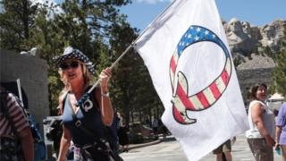 A Donald Trump supporter holding a QAnon flag visits Mount Rushmore National Monument on 01 July 2020