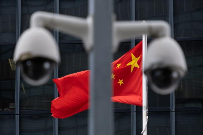 © Bloomberg. The flag of China is flown behind a pair of surveillance cameras outside the Central Government Offices in Hong Kong, China, on Tuesday, July 7, 2020. Hong Kong leader Carrie Lam defended national security legislation imposed on the city by China last week, hours after her government asserted broad new police powers, including warrant-less searches, online surveillance and property seizures. Photographer: Roy Liu/Bloomberg