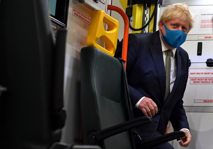 Prime Minister Boris Johnson, wearing a face mask, boards an ambulance to talk with a paramedic during a visit to the headquarters of the London Ambulance Service NHS Trust on July 13, 2020 in London.