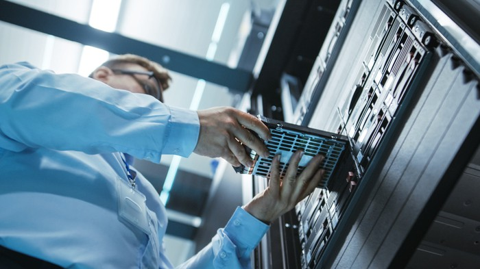 An engineer placing a hard drive into a server tower in a data center.