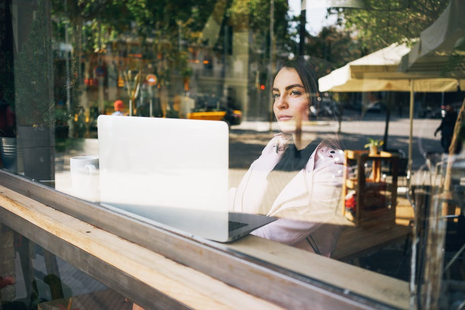 Woman sits in cafe with laptop