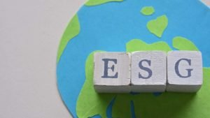 """Wooden blocks spell out """"ESG"""" over a flat illustration of the earth. esg investing"""