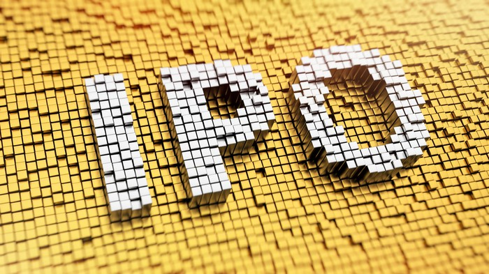 White mosaic tiles spelling IPO on a yellow mosaic tile background.
