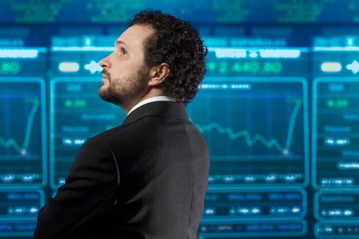 A businessman looking at a digital stock big board.