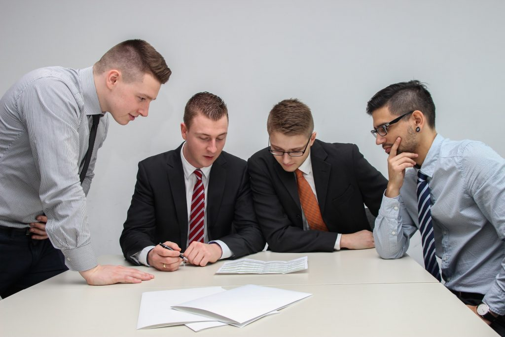 Four people looking at paper on a table