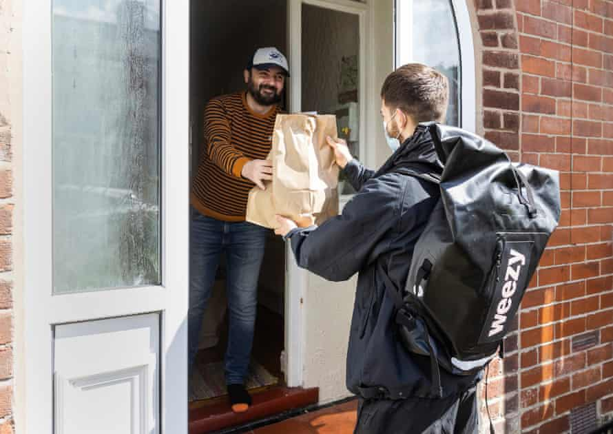 Sean Holehouse delivers a Weezy order to the home of Salford resident Glenn Cobane.