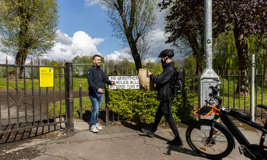 Student Tyler Kernick, 25, receives his shopping from Weezy rider Matthew Wright in a park as he livesjust outside the delivery area in Salford.