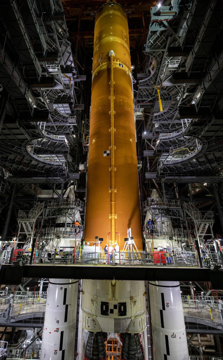 epa09275198 A handout picture made available by the National Aeronautics and Space Administration (NASA) shows teams with NASA's Exploration Ground Systems and contractor Jacobs lowering the Space Launch System (SLS) core stage - the largest part of the rocket - onto the mobile launcher, in between the twin solid rocket boosters, inside High Bay 3 of the Vehicle Assembly Building at NASA's Kennedy Space Center (KSC) in Florida, USA, 12 June 2021 (issued 16 June 2021). The 188,000-pound core stage, with its four RS-25 engines, will provide more than two million pounds of thrust during launch and ascent, and coupled with the boosters, will provide more than 8.8 million pounds of thrust to send the Artemis I mission to space. Under the Artemis program, NASA will land the first woman and first person of color on the Moon, as well as establish a sustainable presence on the lunar surface in preparation for human missions to Mars. EPA/NASA/CORY HUSTON HANDOUT HANDOUT EDITORIAL USE ONLY/NO SALES