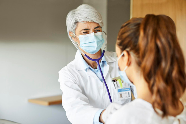 Medical worker examining female patient through stethoscope in ICU. Healthcare professional is looking at sick woman in hospital. They are wearing protective face mask during COVID-19 pandemic.