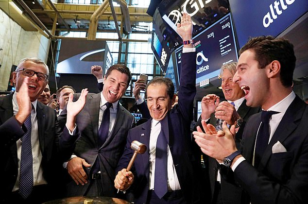 Hammering down costs: Patrick Drahi (centre) celebrates his firm Altice¿s New York flotation. He has now bought a 12.1 per cent stake in BT