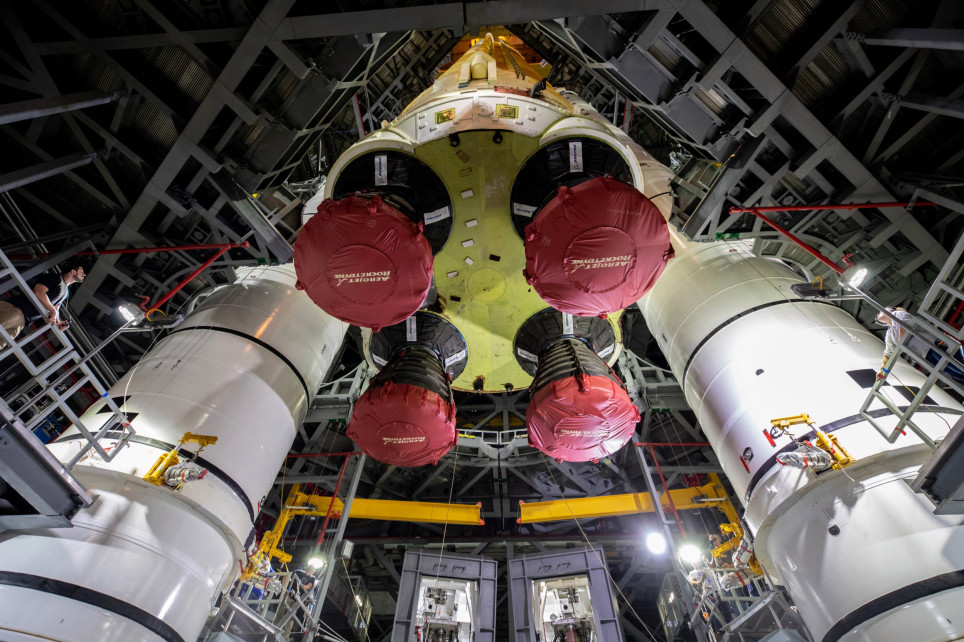 epa09275200 A handout picture made available by the National Aeronautics and Space Administration (NASA) shows teams with NASA's Exploration Ground Systems and contractor Jacobs lowering the Space Launch System (SLS) core stage - the largest part of the rocket - onto the mobile launcher, in between the twin solid rocket boosters, inside High Bay 3 of the Vehicle Assembly Building at NASA's Kennedy Space Center (KSC) in Florida, USA, 12 June 2021 (issued 16 June 2021). The 188,000-pound core stage, with its four RS-25 engines, will provide more than two million pounds of thrust during launch and ascent, and coupled with the boosters, will provide more than 8.8 million pounds of thrust to send the Artemis I mission to space. Under the Artemis program, NASA will land the first woman and first person of color on the Moon, as well as establish a sustainable presence on the lunar surface in preparation for human missions to Mars. EPA/NASA/CORY HUSTON HANDOUT HANDOUT EDITORIAL USE ONLY/NO SALES