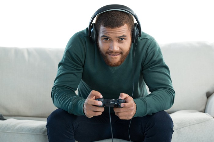 Gamer wearing headphones and holding a controller on the couch.