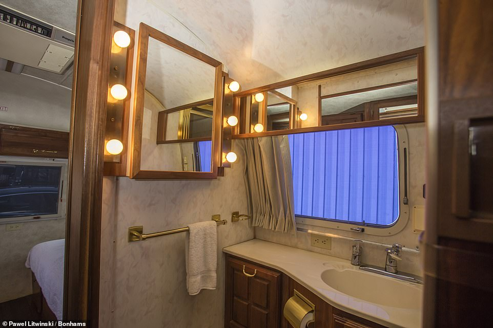 There are plenty of mirrors in the tiny bathroom, with lots of Hollywood lighting and enough space for a towel rail