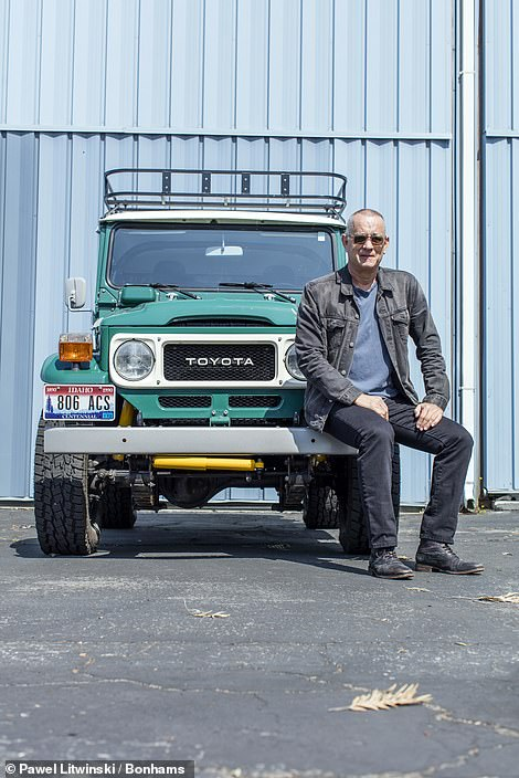 Tom Hanks pictured with his bespoke Land Cruiser, which isset to sell for between $75,000 and $125,000 (£55,000 and £91,000)