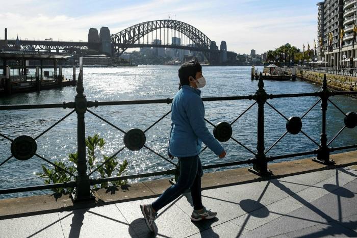 A woman wearing a face mask walks along a quiet Circular Quay in Sydney