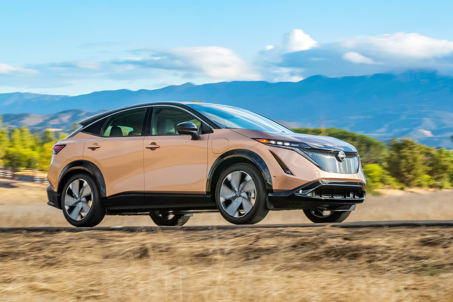 The new electric crossover from Nissan, the Ariya, driving in the sunlight with mountains in the background