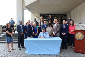 Governor Carney signs Senate Bill 15 at a table and surrounded by legislators and advocates