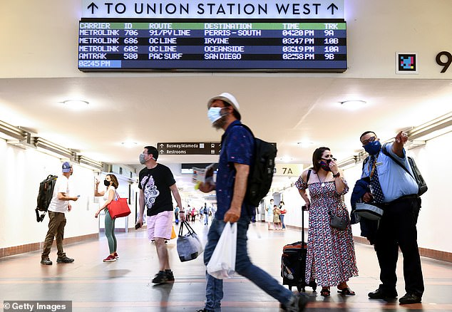 CDC will recommend on Tuesday that fully vaccinated Americans put masks back on indoors in COVID-19 hotspots. Pictured: People wear face coverings as they pass through Union Station in Los Angeles, California, July 2021