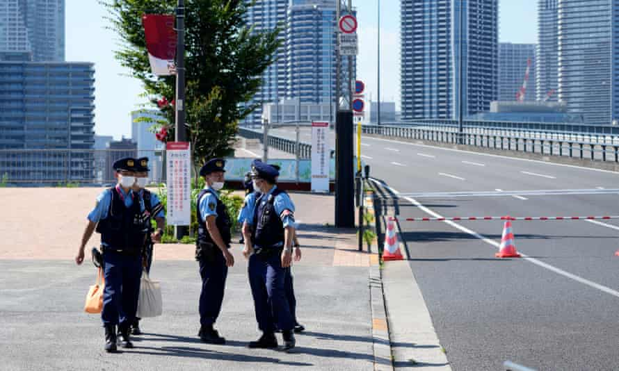 Police officers gather at the Olympic village, where a first positive Covid case was confirmed.