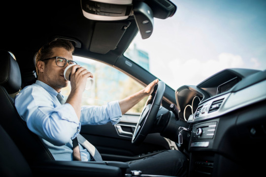 Close up photo of a businessman driving a car while drinking coffee
