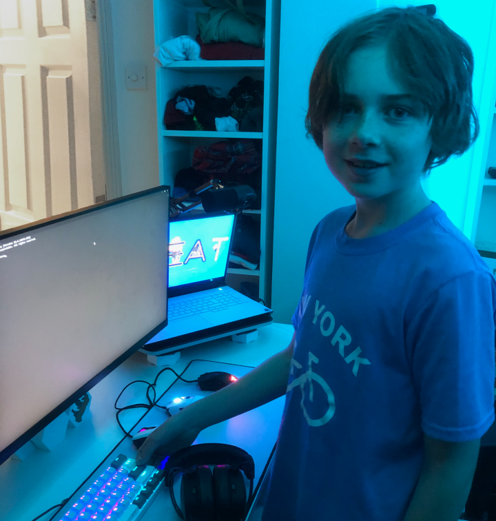 Jaeden, standing in front of two computer screens, with his hand next to his keyboard. He is wearing a blue tshirt and the room is lit up blue