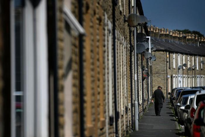 A man walks down a terraced street in Burnely