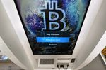 FILE - In this Feb. 9, 2021, file photo, the Bitcoin logo appears on the display screen of a cryptocurrency ATM at the Smoker's Choice store in Salem, N.H. China's central bank on Friday, Sept. 24, 2021, declared all transactions involving Bitcoin and other virtual currencies illegal, stepping up a campaign to block use of unofficial digital money.