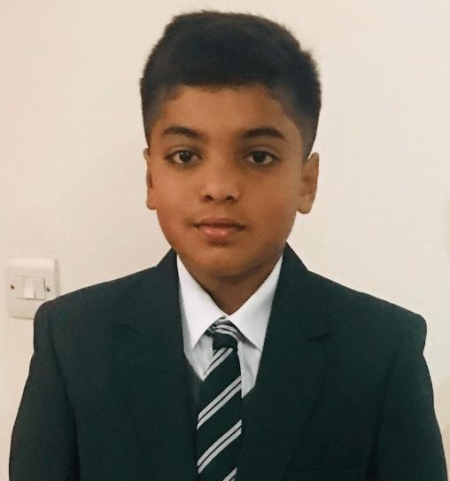 Ansh in his school uniform - a black blazer, white shirt and a black and white striped tie.