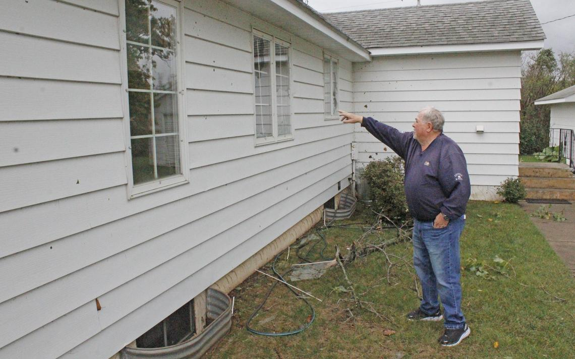 Dick Carpenter points out broken windows, dents in the siding and debris plastered all over the back of his house Sunday, Oct. 10, 2021 after a tornado touched down in his yard on Saturday. Robin Fish / Park Rapids Enterprise