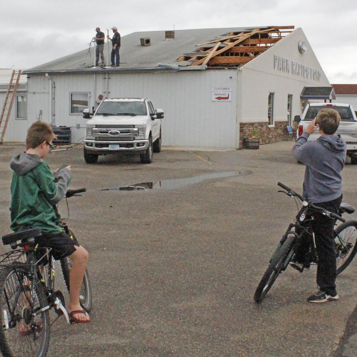 Aiden Fraki, left, and Aiden Bera take pictures of the damage at Park Rapids Ford on Sunday, Oct. 10, 2021 after a tornado tore the roof off the dealership's showroom Saturday night. Repairing damage to the building's wiring are Josh Hoffman, Mark Hellcamp and Brandon Chase with Hoffman Electric. Robin Fish / Park Rapids Enterprise