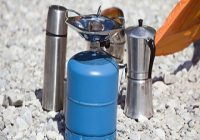 Der Campingkocher. Gas Campingkocher neben Expressomaschiene und Thermoskanne.