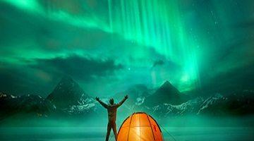 Das Zelt. Ein Mann, der in den wilden Nordbergen mit einem belichteten Zelt kampiert, das eine großartige grüne Nordlichter-Auroradarstellung ansieht.